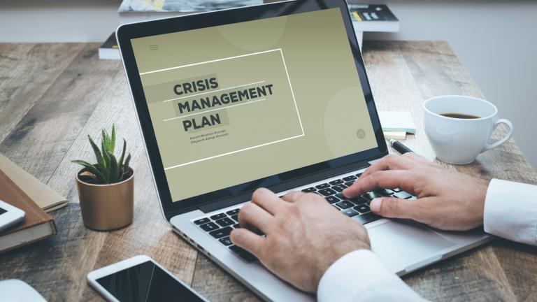 CRISIS MANAGEMENT PLAN on a laptop