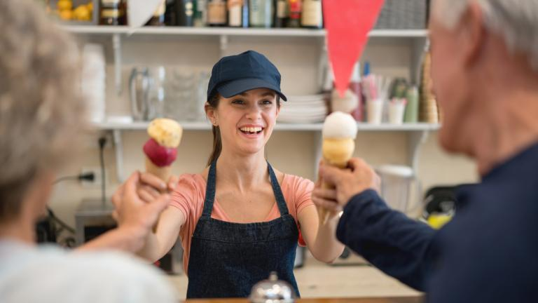 Friendly saleswoman at the ice cream parlor serving ice cream to senior customers