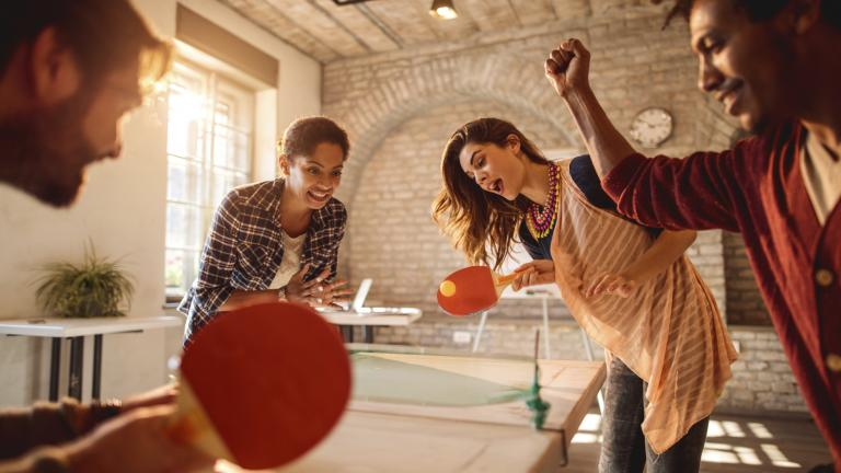 Happy businesswomen playing table tennis against happy businessmen