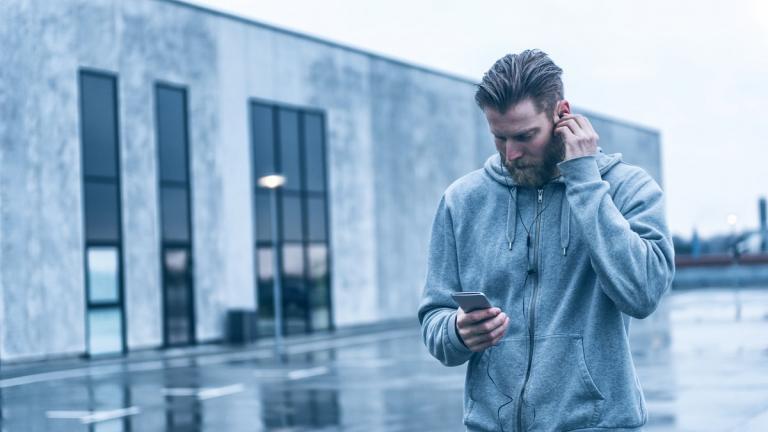 Man standing using iphone