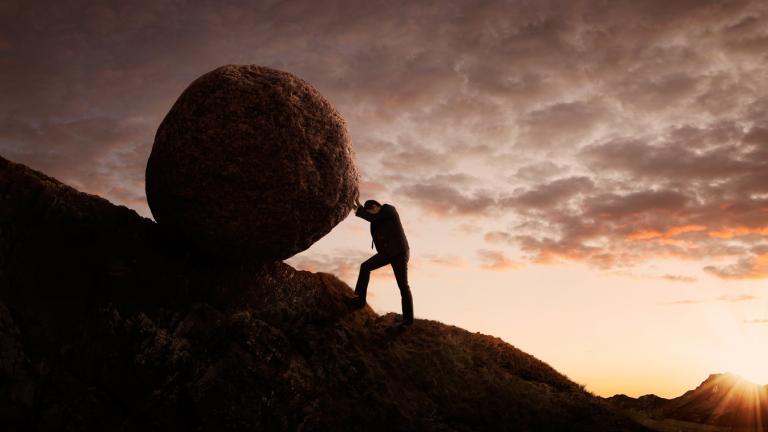 Man pushing rock up hill