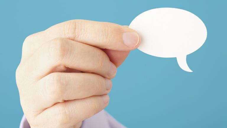 Hand holding speech bubble
