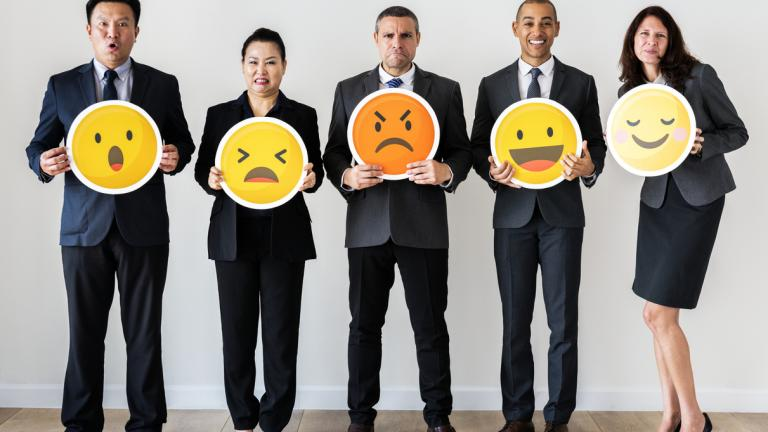 business people holding emoji symbols