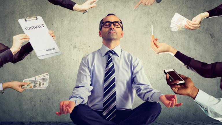 business man meditating to relieve stress of busy corporate life
