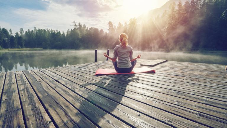girl meditating by lake