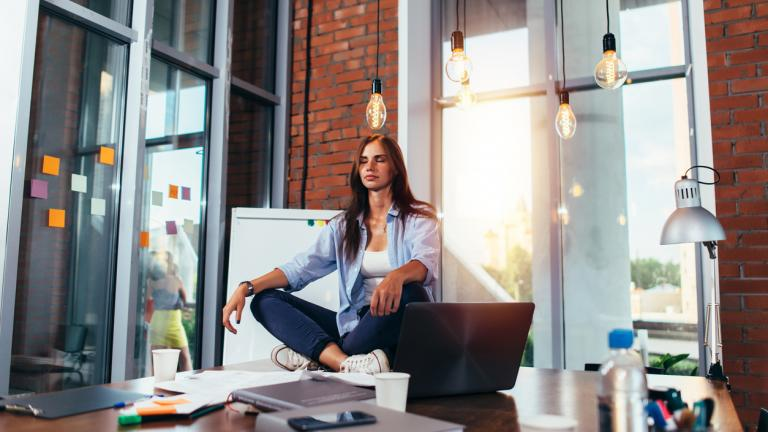 woman meditating on office desk