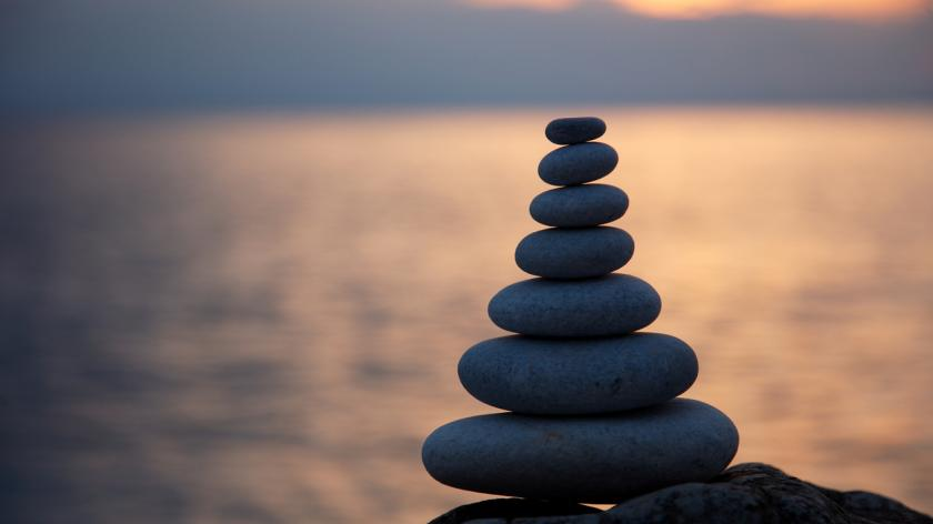 Stack of seven pebbles at sunset