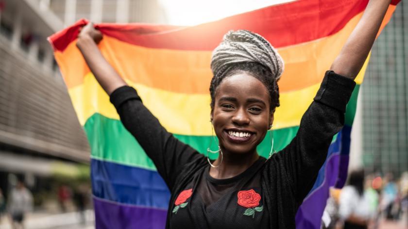 Woman Waving Rainbow Flag at Pride Parade