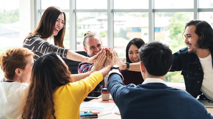 Group of young multiethnic diverse people gesture hand high five, laughing and smiling together in brainstorm meeting at office