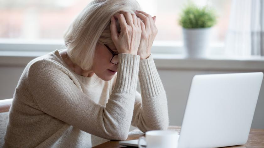 woman in front of laptop looking stressed