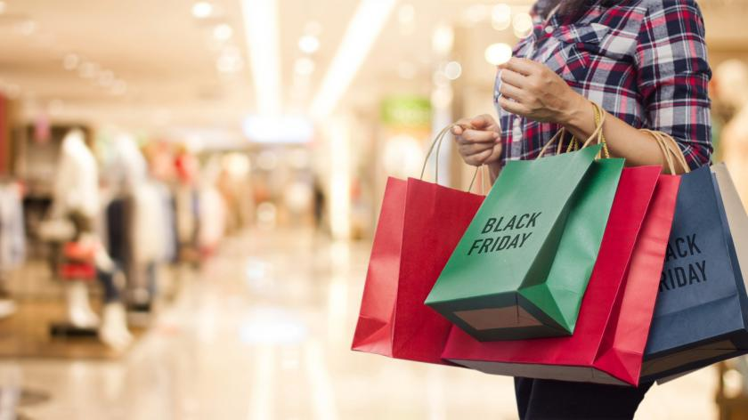 Black Friday, Woman holding many shopping bags while walking in the shopping mall background