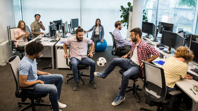 Young computer programmers having fun while playing with soccer ball in the office.
