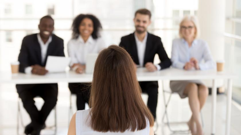 Back view of female job applicant make good first impression at work interview in office, millennial woman candidate talk, impress HR managers or recruiters at hiring.