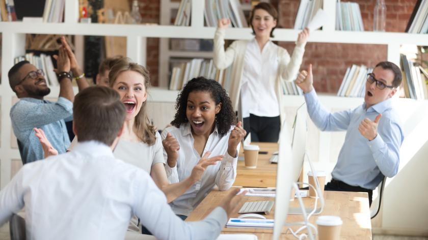 Male worker share good news with multiracial colleagues in shared workplace, diverse employees scream with happiness excited with corporate success or goal achievement, team celebrating win