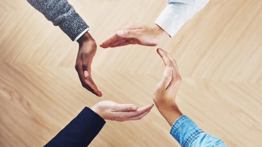 High angle shot of a group of unidentifiable businesspeople forming a circle with their hands