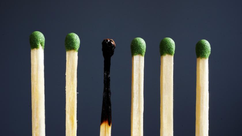 Burnout at work and over exhausted concept. Line of matches and one burnt.
