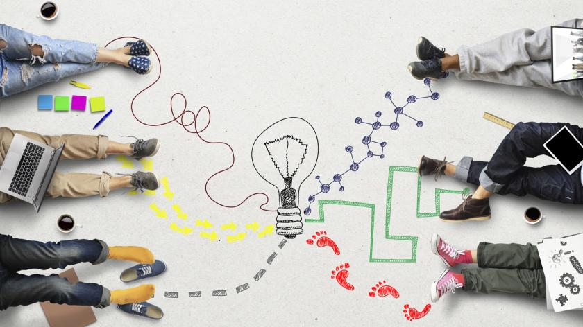 image of an illustrated lightbulb, signifying innovation with different employees feet around it