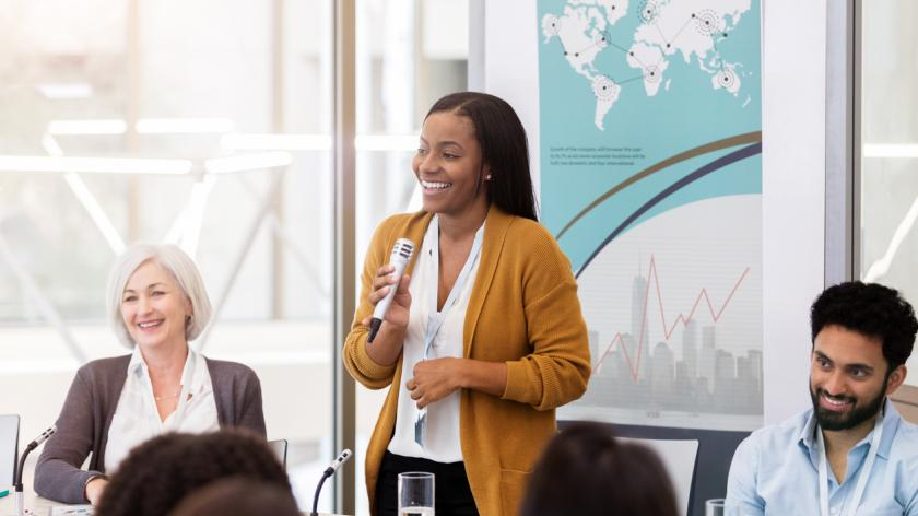 black woman giving a presentation to multi-ethnic business team