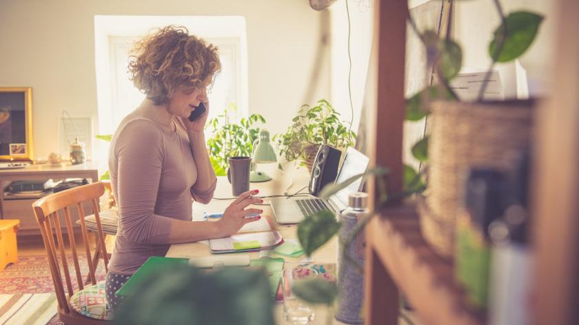 woman working from home at a desk on the telephone