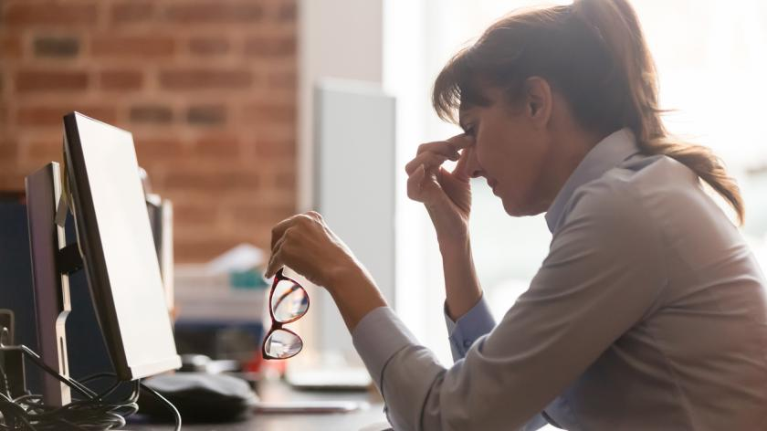Stressed overworked middle aged businesswoman office worker taking off glasses