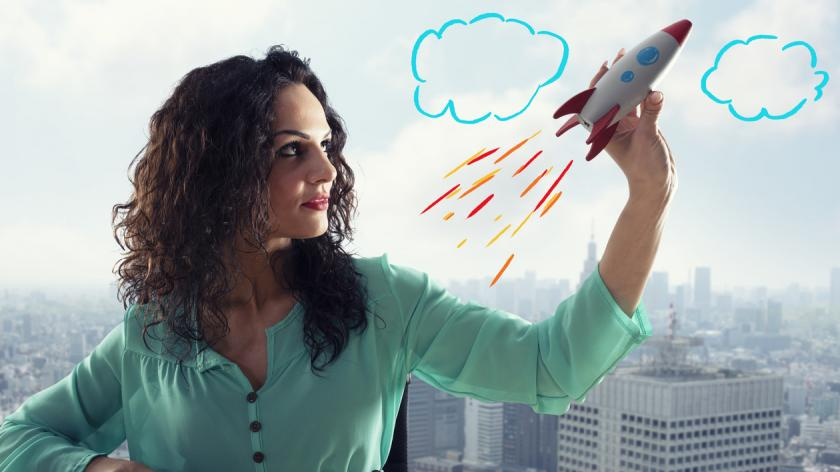 Businesswoman launches his company with a toy rocket. Concept of startup and innovation