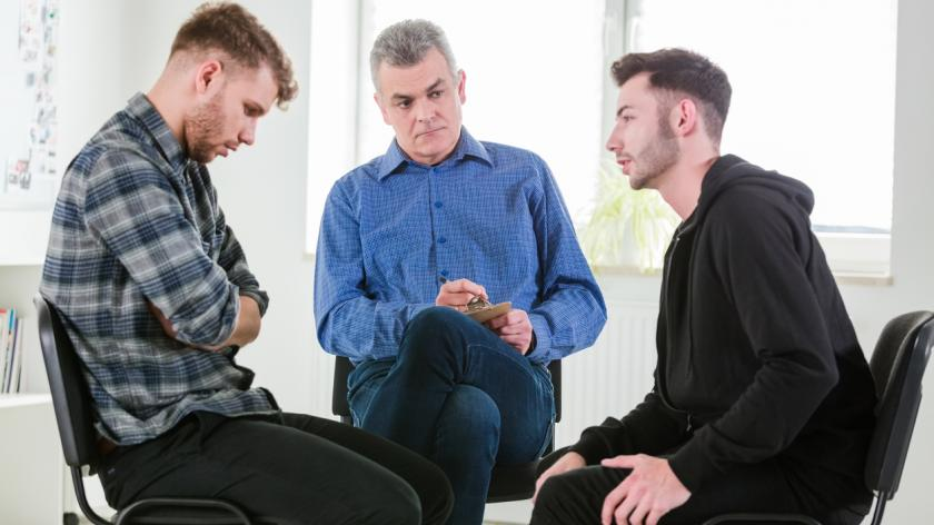 Male students discussing problems by social worker