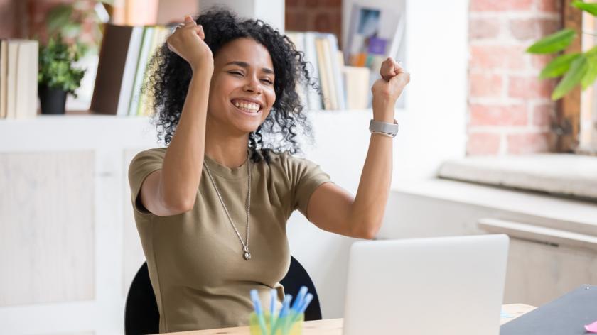 Home working employee celebrating at laptop