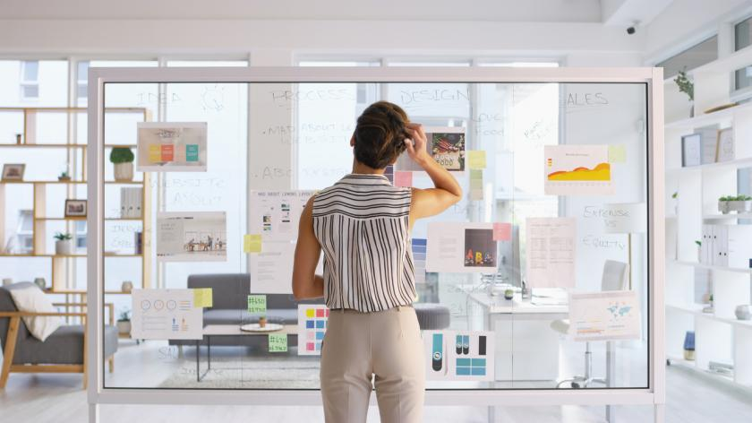 Businesswoman writing down ideas on a glass wall in her office