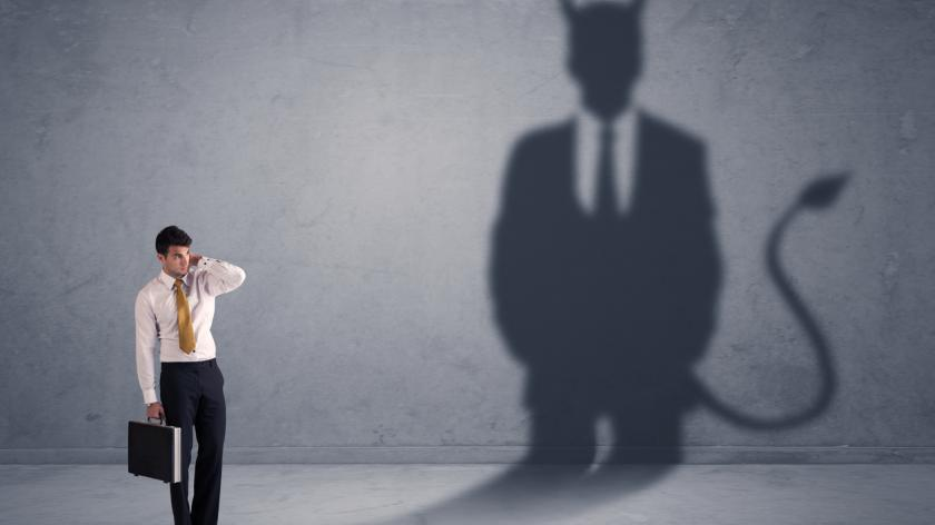 Business man looking at his own devil demon shadow concept background