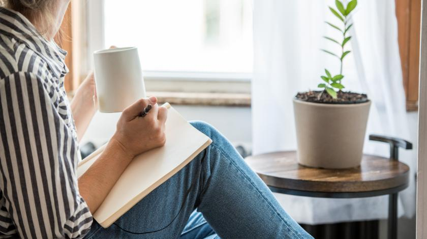 A young woman takes a break to do something analog like writing in her journal and drinking tea.
