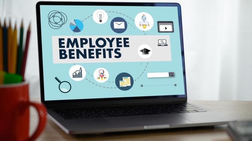 laptop on a desk showing employee benefits graphic on screen