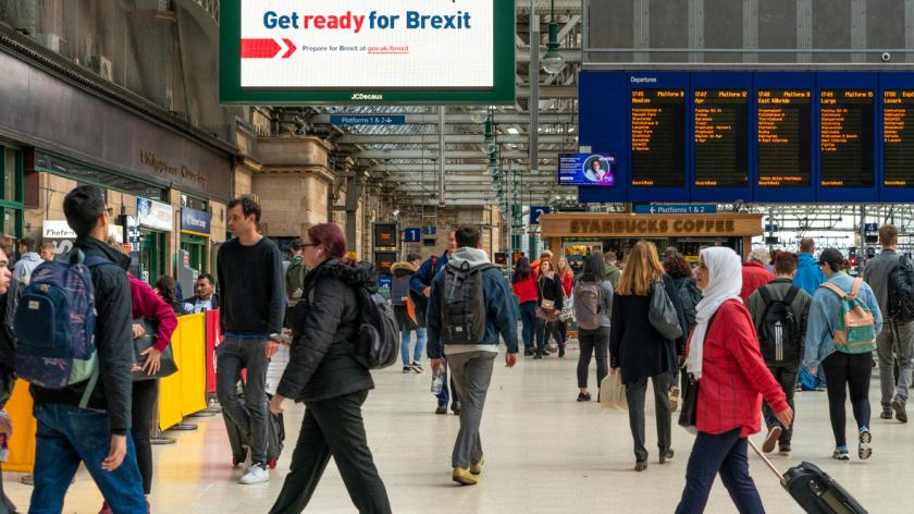 Glasgow, Scotland - Passengers in Central Station walking in front of a UK government sign advising people to prepare for Brexit.