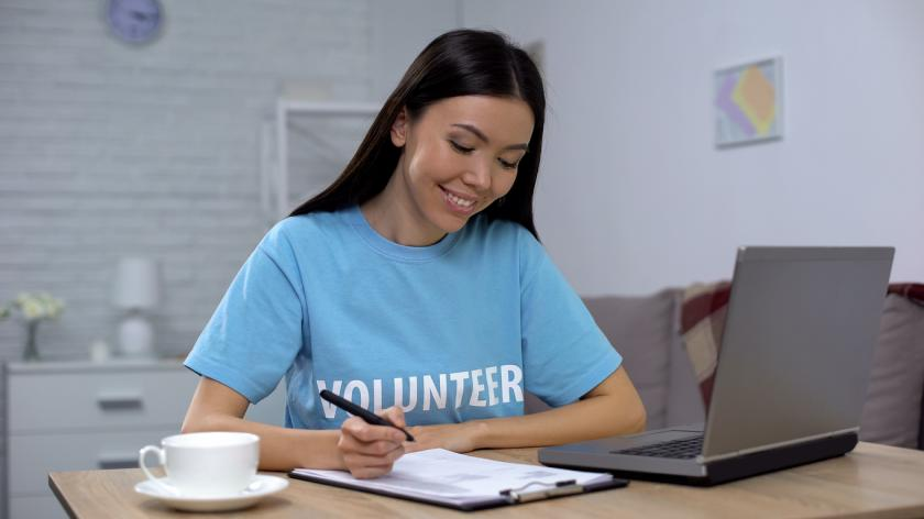 Female volunteer working laptop and writing notes sitting table, charity project