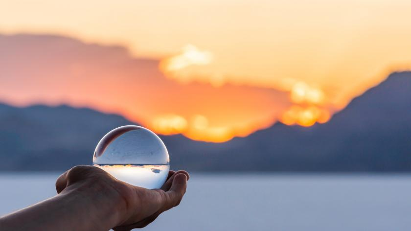hand holding crystal ball near Salt Lake City, Utah and mountain view and sunset