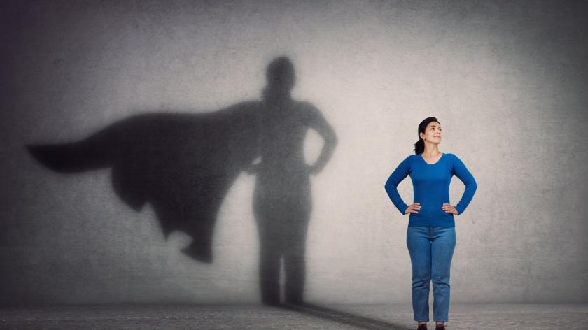 Brave woman keeps arms on hips, smiling confident, casting a superhero with cape shadow on the wall.