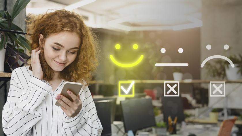 happy employee completing employee survey on her smartphone