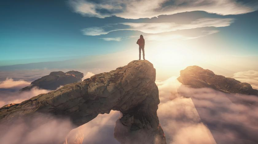 Traveler with a backpack standing on a mountain peak above clouds.