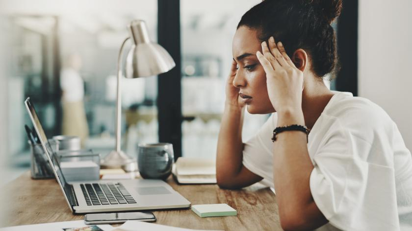 Shot of a young businesswoman looking stressed while using a laptop in her home office
