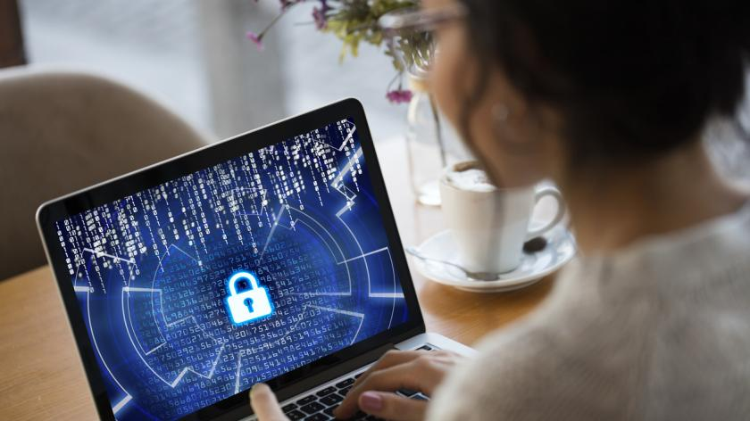 woman working on a laptop with a cyber security icon on it