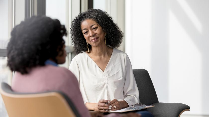 The mature adult female therapist listens compassionately to the unrecognizable female client share her problems.