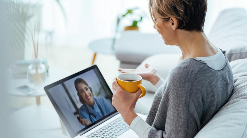 Woman sitting on the sofa while making video call over laptop with her doctor.