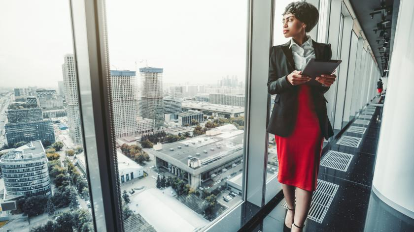 woman entrepreneur in a red skirt and black jacket is using a digital tablet while leaning against a panoramic window of a business office high-rise
