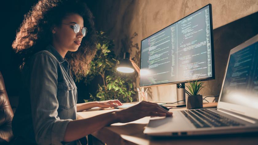 Women in tech job sat at computer coding