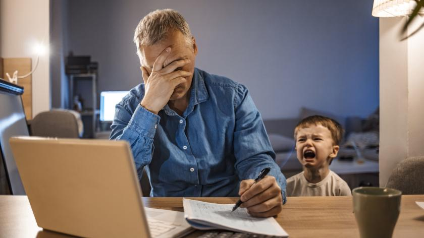 Busy mature businessman working from home and watching his crying son at night, who is is yelling at him.