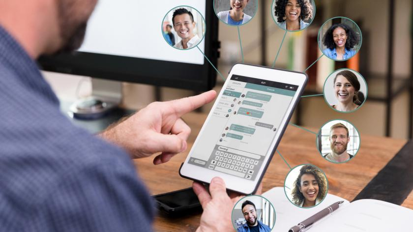 While using a digital tablet, a mid adult man chats with a large group of friends or business associates.