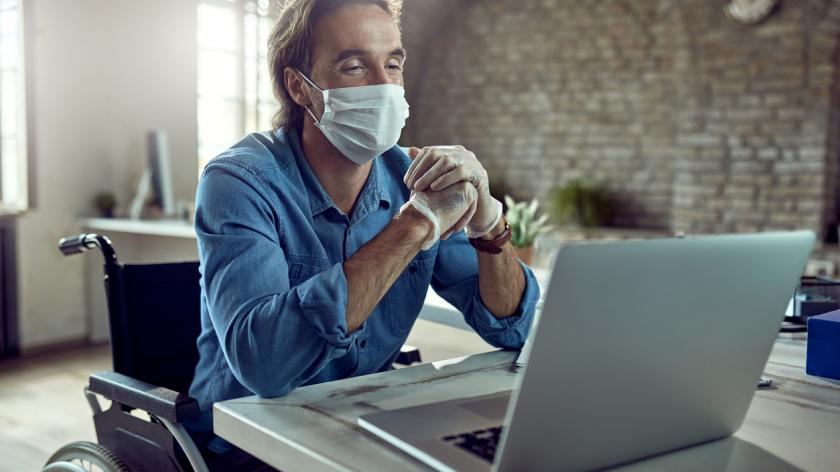 Happy businessman in wheelchair wearing face mask while having video call over laptop in the office during virus epidemic.