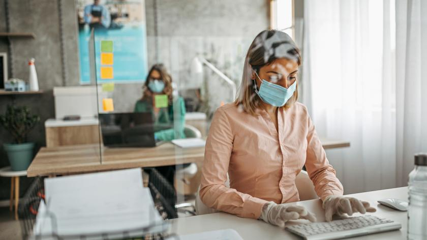 Two businesswomen working at office wearing protective gloves and face mask maintaining social distance.