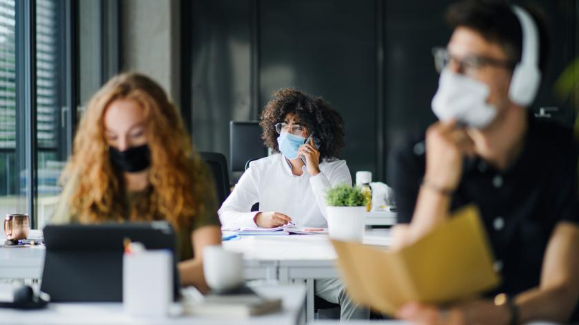 Young people with face masks back at work in office after coronavirus quarantine and lockdown.