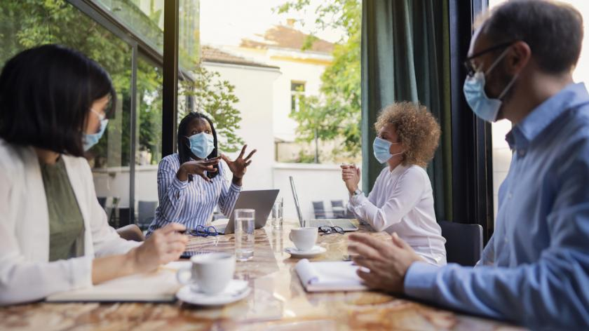 diverse group of business people in social distanced meeting wearing masks