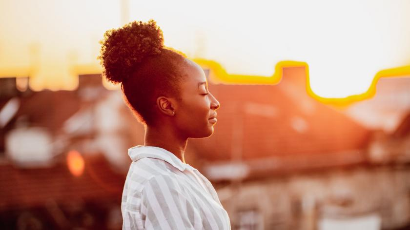 woman is on the balcony at sunset practicing mindfulness